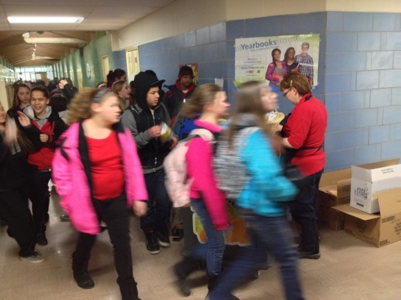 Lots of students moving past a Grab-n-Go Breakfast Cart